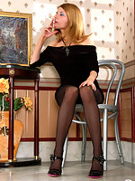 Lustful chick in nylon black pantyhose looking at a picture while smoking