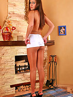 Extremely tempting chick in flesh-colored pantyhose posing by the fireplace