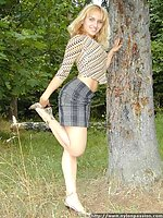Young cute girl shows her pussy through gauzy pantyhose outdoors