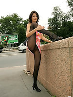 Mischievous babe in black pantyhose knowing the best way of posing outdoors