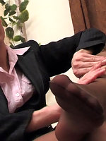 Naughty business lady massaging her nyloned feet with her skillful hands