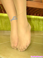 Horny shemale in high heel shoes pulling down her sheer-to-waist pantyhose