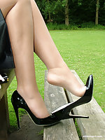 Hot blonde Milf Jess shows her shiny black heels and stockings all round her insolent short office skirt