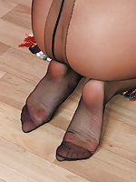 Salacious gal can't help sniffing her tempting feet clad in black pantyhose